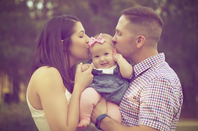 mum and dad kissing baby girl