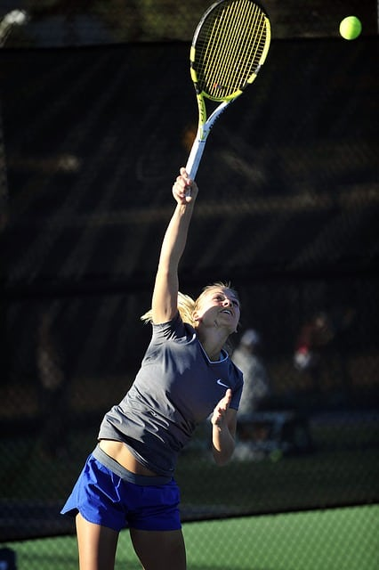female tennis player taking a serve