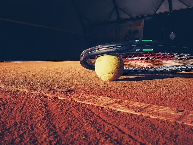 tennis ball and racket on clay court