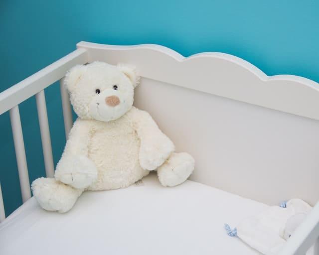 white crib with bear
