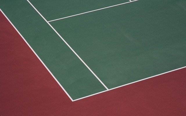 green tennis court with red surrounding