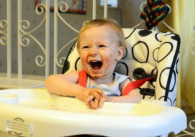 messy toddler in high chair